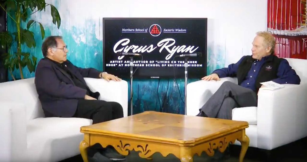 two men sitting in chairs on a TV interview set