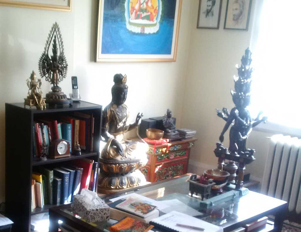 an office space with a shelf of books and a number of Buddhist statues