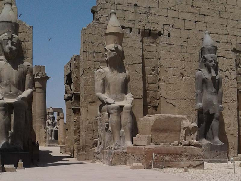 large statues outside the ruins of an ancient structure