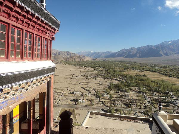 view from red building with mountains trees and small buildings in the background