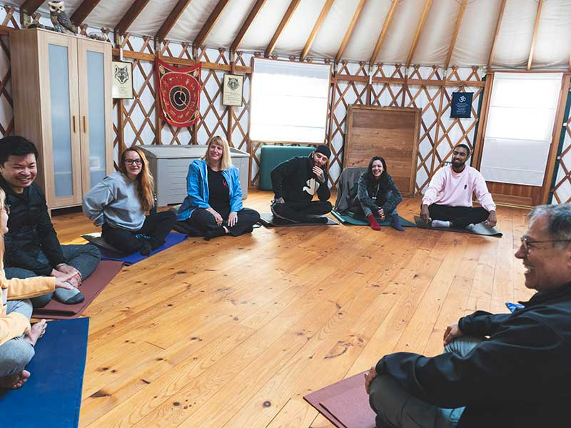 room of men and women sitting on mats